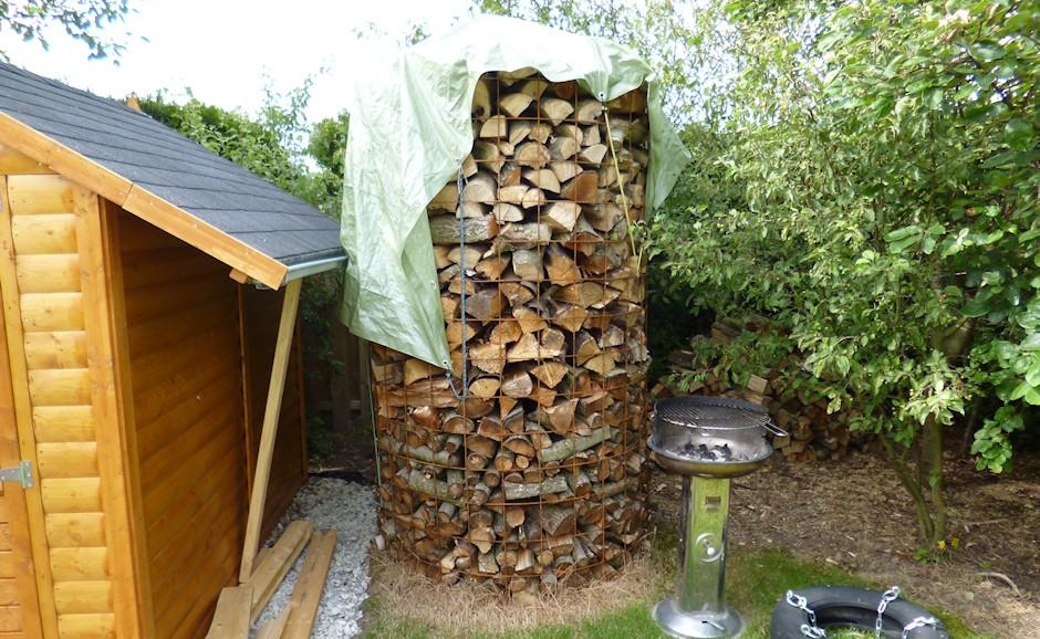 Feuerholz rund gestapelt und abgedeckt